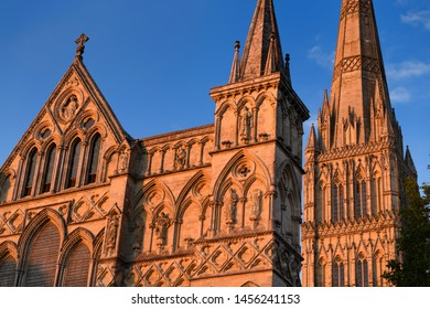 Great West Front facade of Salisbury Cathedral with statuary of Saints and Angels and Spire in red last light in Salisbury England