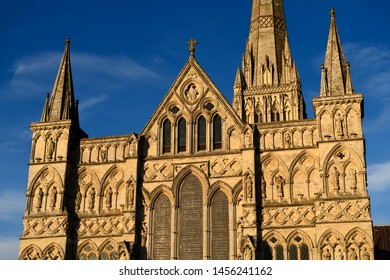 Great West Front facade of Salisbury Cathedral with statuary of Saints and Angels in gold evening light in Salisbury England