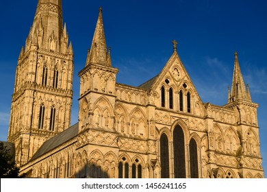 Great West Front facade of Salisbury Cathedral with statuary of Saints and Angels and Spire in gold evening light in Salisbury England