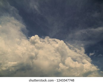 Great white cumulonimbus cloud with gray shadows, occupying the base of the image, under a blue ceus with scattered clouds, north coast of Sao Paulo, Brazil