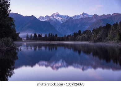 Great winter panorama of the Lake Matheson.  Purple morning scene of New Zealand.  Dramatic morning view and spectacular winter sunrise.