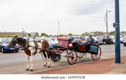 Great Yarmouth, Norfolk, UK – June 01 2019. A horse and carriage owner sitting in the carriage waiting for tourists to request a horse and carriage ride up the Golden Mile, Great Yarmouth, Norfolk