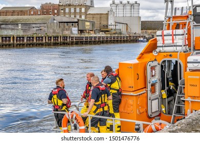 Great Yarmouth, Norfolk, UK – September 08 2019. Five members of Great Yarmouth and Gorleston RNLI lifeboat crew standing on the rear deck of the offshore lifeboat chatting