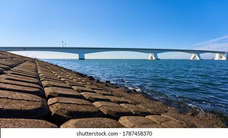 Great Zeeland Bridge, dam made of stone blocks, deep blue sea water and cloudless sky. Netherlands, Zeeland.