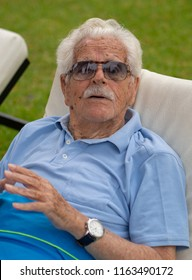 Great-grandfather, 100 years old, is relaxed in the garden of his home.