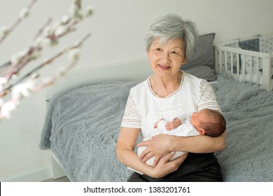 Great-grandmother holds a newborn great-granddaughter in her arms. A grandmother with gray hair is nursing a little granddaughter. Grandmother holding her granddaughter by the handles