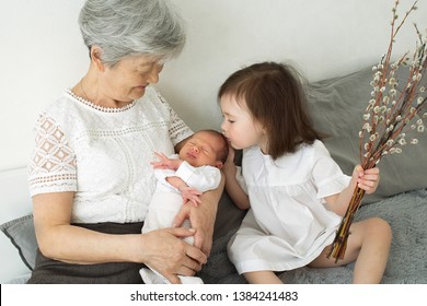 Great-grandmother hugs two great-granddaughters. Grandmother sits with two granddaughters. Granddaughters hug their beloved grandmother