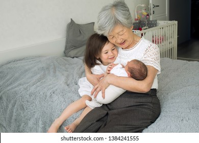 Great-grandmother hugs two great-granddaughters. Grandmother sits with two granddaughters. Granddaughters hug their beloved grandmother. Grandmother with child