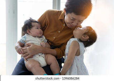 Great-grandmother hugs two great-granddaughters. Grandmother sits with two granddaughters. Granddaughters hug their beloved grandmother. Grandmother with child - Image