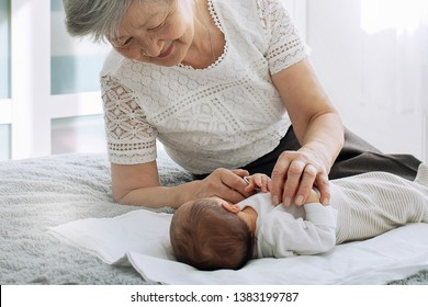 Great-grandmother plays with a newborn great-granddaughter. A grandmother with gray hair is nursing a little granddaughter. Grandmother holding her granddaughter by the handles
