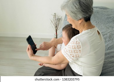 Great-grandmother sits with great-granddaughter and looks into the smartphone. Grandmother and granddaughter take a selfie on a smartphone. Grandmother with her granddaughter look into the phone