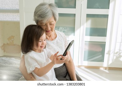 Great-grandmother sits with great-granddaughter and looks into the smartphone. Grandmother and child take a selfie on a smartphone. Grandmother with her granddaughter look into the phone.