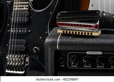 The greatness of musical instruments is depicted in the photo. Statuesque guitar with strings, various types of harmonica and an amp.