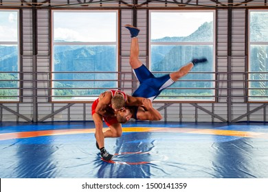 Greco-Roman wrestling training, grappling. Two greco-roman  wrestlers in red and blue uniform making a thigh throw  on a wrestling carpet in the gym.The concept of male wrestling and resistance