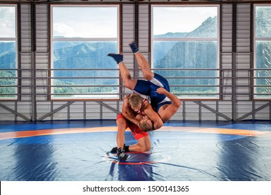 Greco-Roman wrestling training, grappling. Two greco-roman  wrestlers in red and blue uniform wrestling  on a wrestling carpet in the gym.Training and practicing sports throws