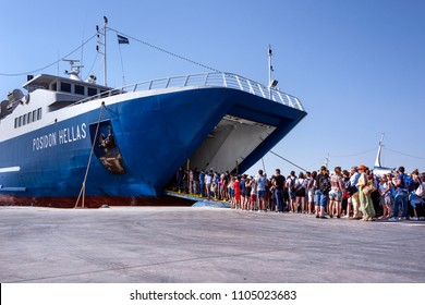 Greece, Aegina: People residents tourists men women enter a big ferry at the port of famous Greek island with skyline, boats, ferries and blue sky - concept travel transport leisure. April 28, 2018