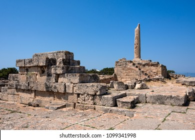 Greece, Aegina: Ruin of famous Temple of Apollo with sun, collumn and blue sky - concept history travel. The patron of Delphi, Apollo was an oracular god, the prophetic deity of the Delphic Oracle.
