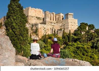 Greece, Athens, Areopagus: Young women look at Propylaea and Beule Gate of famous Acropolis, green park trees, horizon and blue clear sky in the city center of the Greek capital. April 25, 2018