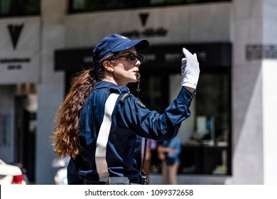 Greece, Athens: Daily street scene with police officer woman in blue uniform, whistle and white gloves in the city center of the Greek capital - concept traffic regulation control. April 26, 2018