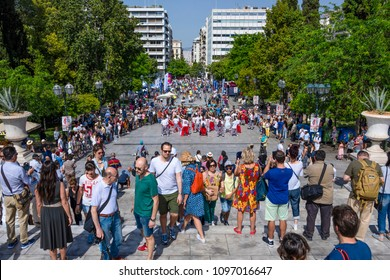 Greece, Athens: Famous Syntagma square with central water fountain, people, residents, women, men, park, green trees in the city center of the Greek capital and blue sky in background. April 29, 2018