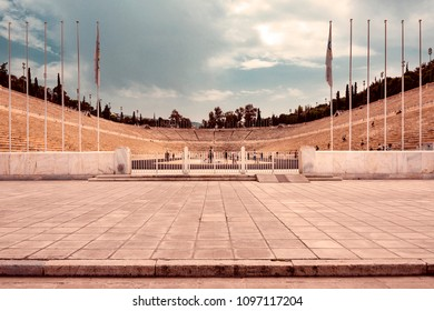 Greece, Athens: Group of people tourists residents men women visit the famous Panathenaic Stadium in the city center of the Greek capital - dramatic retro vintage look design. April 29, 2018