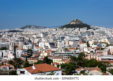 Greece, Athens, Lycabettos: Sunset panorama view of famous majestic Mount Lycabettus hill in the city center of the Greek capital with skyline horizon and blue sky in the background. April 25, 2018