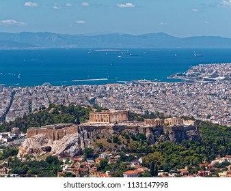 Greece, Athens panoramic view with parthenon temple on acropolis hill and Plaka old neighborhood, Piraeus harbor in the background