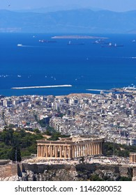 Greece, Athens panoramic view with parthenon temple on acropolis hill, Plaka old neighborhood and Saronic golf on the distant background