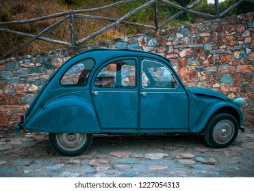 GREECE - AUGUST 16th, 2018: blue retro car Citroen 2CV on stone wall background