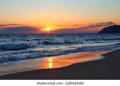 Greece beach sunset in Corfu island. Agios Gordios and Ionian Sea.