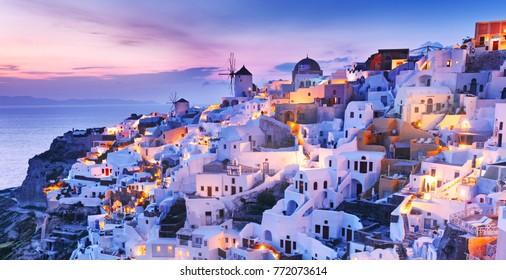 Greece. Charming twilight scenery of town Oia - IA skyline on Wonderful island Santorini in warm waters of Greek Aegean Sea, Mediterranean region. Wonderful lights of night town at slope of volcano.