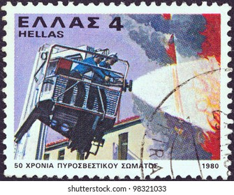GREECE - CIRCA 1980: A stamp printed in Greece issued for the 50th anniversary of fire brigade shows a firefighting squad, circa 1980.