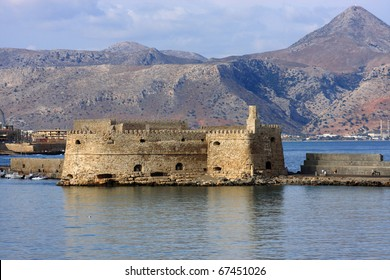 Greece Crete Heraklion Venetian Fortress Rocca al Mare at harbor entrance with mountains in background