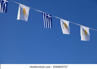 Greece and Cyprus flags banner against blue sky.