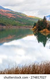 Greece Doksa lake among mountains and trees by winter