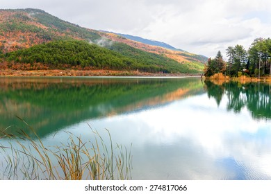 Greece Doksa lake among mountains and trees by winter