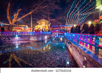 """Greece, Drama - December 25, 2018: Night view of the greek Christmas market """"Oneiroupoli"""" with lights, figurines around the river in Drama, Greece"""