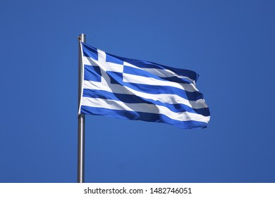 Greece flag on flagpole. Soars in the wind. Blue sky, sunny day