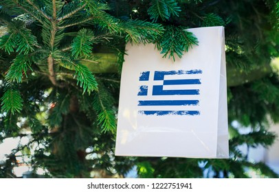 Greece flag printed on a Christmas shopping bag. Close up of a shopping bag as a decoration on a Xmas tree on a street. New Year or Christmas shopping, local market sale and deals concept.