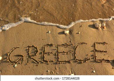 Greece Hand Written on Sandy Beach with Pebbles and Sea Water Splash Background. Vacation Holiday Honeymoon Travel Tourism Vacation Seascape Greek Islands Resorts Couple Goals Happiness Banner Image.