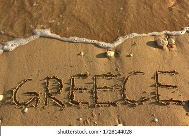 小石と水しぶきの背景に砂浜に書かれたギリシャの手。 バケーションホリデーハネムーン旅行観光バケーションシースケープギリシャ諸島リゾーツカップルゴールハピネスバナー画像