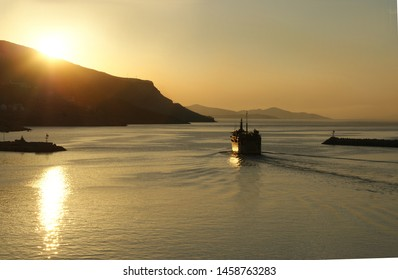 Greece, the island of Kalymnos. Dawn, and as the sun rises, the early morning inter island ferry starts out on it's journey by leaving the harbor at Pothia.