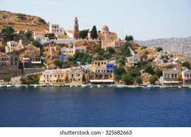 Greece. Island Symi (Simi). Colorful houses in the Mandraki harbor. In blur style
