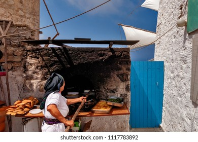 GREECE, KARPATHOS island, OLYMPOS, woman in traditional clothes stuffs breads and ready meals