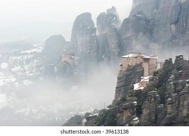 Greece. Meteora. View on Roussanou and Agios Nikolaos Anapaphas monasteries, enveloped by the winter mist