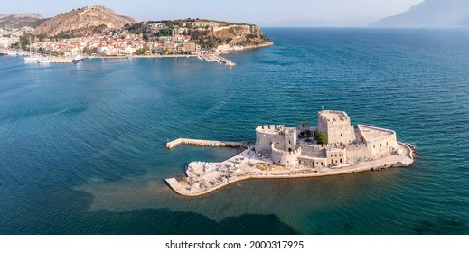 Greece, Nafplio city and Bourtzi, Venetian water fortress at the entrance of the harbour. Aerial drone view. Peloponnese old town cityscape, Blue sky, rippled sea background.