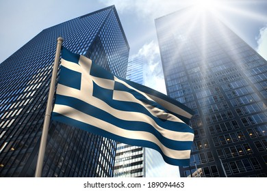 Greece national flag against low angle view of skyscrapers
