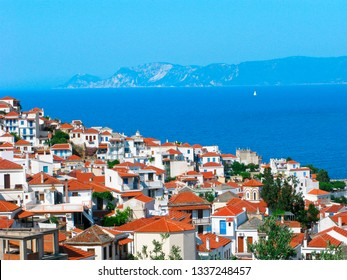 Greece, Northern Sporades, Skopelos island.  Sunny Skopelos town with white houses and red roofs on background of Aegean sea. On the horizon is Alonissos island and a white sailboat.