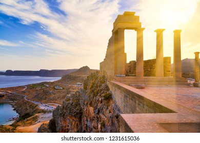 Greece. Rhodes Island. Sun's rays cut through the columns Acropolis of Lindos. View from the height of the ancient temple of Athena Lindia IV century BC to St. Paul's Bay in the form of the heart