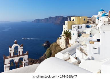 Greece. Santorini island. The beautiful village of Oia with white Cycladic houses with round roofs and a traditional arched bell tower on a sunny day. Narrow streets without tourists